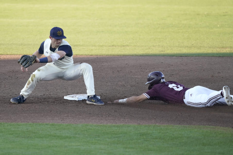 Mississippi State's Kamren James (6) slides safely into second base as Notre Dame infielder Zack Prajzner, left, reaches back to catch the ball at an NCAA college baseball super regional game, Monday, June 14, 2021, in Starkville, Miss. (AP Photo/Rogelio V. Solis)