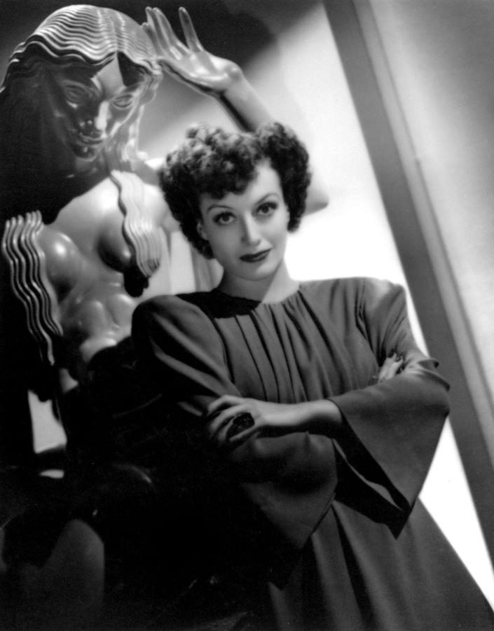 <p>Joan Crawford poses in an A-line dress with pronounced shoulders and bell sleeves. </p>