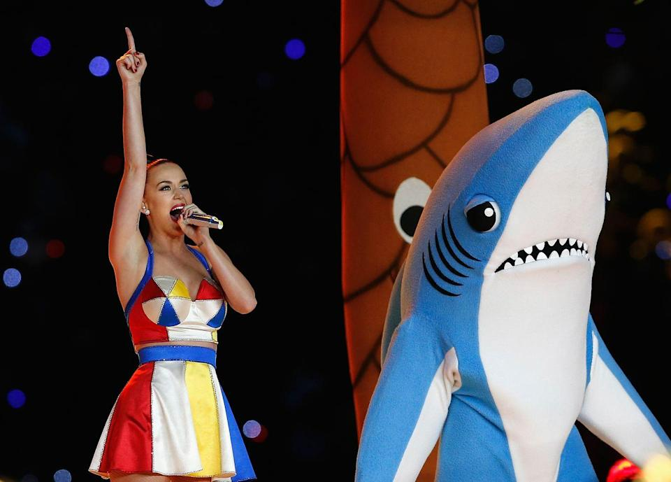 """<p>You can DIY Katy Perry's outfit easily with a little white dress and some color felt strips. All that's left to buy is the shark. </p><p><a class=""""link rapid-noclick-resp"""" href=""""https://www.amazon.com/MH-Inflatable-Costume-Halloween-Costumes/dp/B07VXT937C?tag=syn-yahoo-20&ascsubtag=%5Bartid%7C2140.g.33298559%5Bsrc%7Cyahoo-us"""" rel=""""nofollow noopener"""" target=""""_blank"""" data-ylk=""""slk:Shop shark costume"""">Shop shark costume</a></p>"""