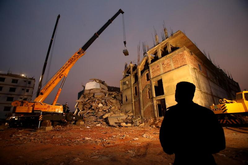 Firefighters and army personnel continue to work as dusk falls as they dislodge the debris and fallen ceiling of the garment factory building which collapsed in Savar, near Dhaka, Bangladesh, Monday, April 29, 2013. Rescue workers in Bangladesh gave up hopes of finding any more survivors in the remains of a building that collapsed five days ago, and began using heavy machinery on Monday to dislodge the rubble and look for bodies. At least 381 people were killed when the illegally constructed, 8-story Rana Plaza collapsed in a heap on Wednesday morning along with thousands of workers in the five garment factories in the building. (AP Photo/Wong Maye-E)