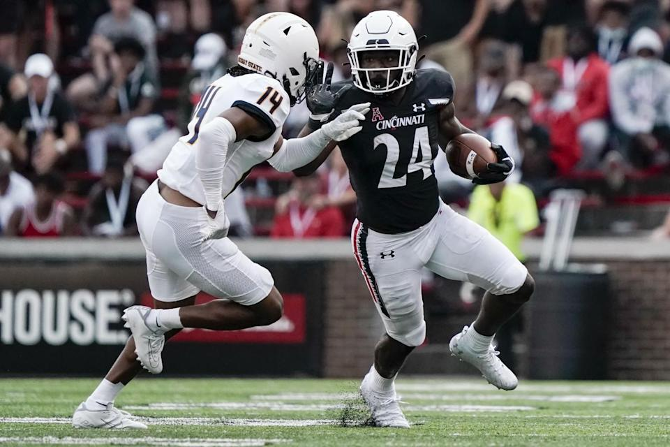 Cincinnati running back Jerome Ford is pushed out of bounds by Murray State cornerback Cayvian Holmes.