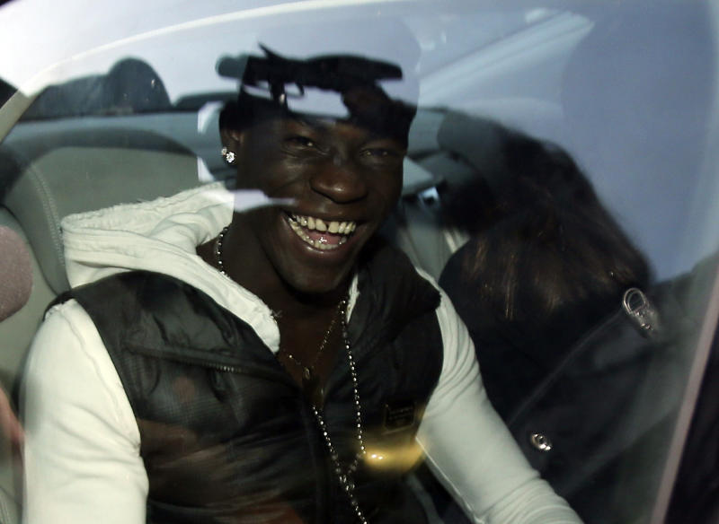 """Mario Balotelli smiles as he arrives in Busto Arsizio, near Varese, Italy, for medical checks, Wednesday, Jan. 30, 2013. AC Milan announced on Tuesday that it has reached an agreement with Manchester City to sign Italy striker Mario Balotelli from the English champions. City declined to comment on reports that a deal had been struck for the 22-year-old forward, who joined the Premier League club from Milan's city rival Inter in 2010. """"An agreement has been reached with Manchester City, Balotelli will have a medical tomorrow and then sign,"""" Milan director Umberto Gandini told The Associated Press. """"If he doesn't pass the medical, it won't happen."""" (AP Photo/Antonio Calanni)"""