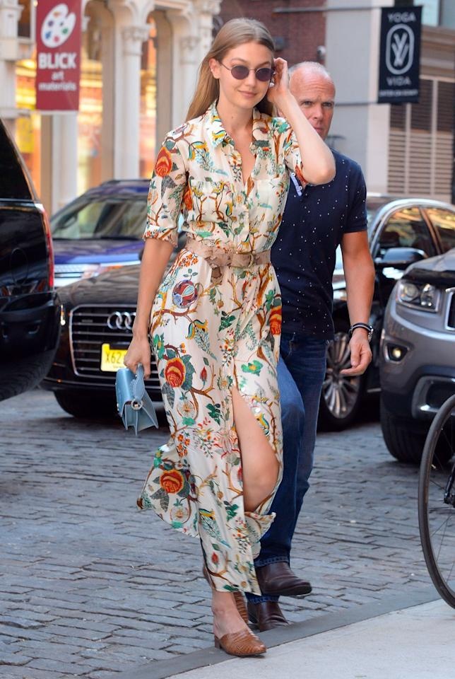 <p>In a floral belted shirtdress, mini blue purse and brown leather mules while out with friends in NYC. </p>