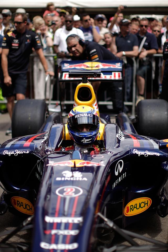 CHICHESTER, ENGLAND - JULY 01:  Red Bull Racing driver Mark Webber climbs into his car in the assembly area prior to a run at the Goodwood Festival of Speed on July 1, 2011 in Chichester, England. Drivers compete in a variety of cars, from vintage models to modern Formula 1 cars in the annual hill climb.  (Photo by Matthew Lloyd/Getty Images)