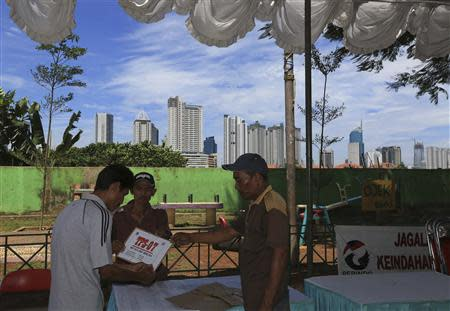 Men hold a sign showing the polling station's number, as the station is prepared for the upcoming parliamentary election in Jakarta