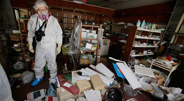 Kazuhiro Onuki wearing white protective gear and a filtered mask stands in his ceramic and craft shop home in Tomioka, Fukushima Prefecture, northeastern Japan. Photo: AP.