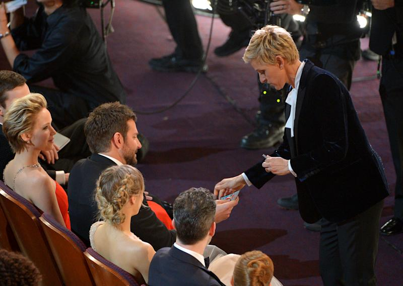 Ellen DeGeneres, right, gives Bradley Cooper a lottery ticket during the Oscars at the Dolby Theatre on Sunday, March 2, 2014, in Los Angeles. (Photo by John Shearer/Invision/AP)