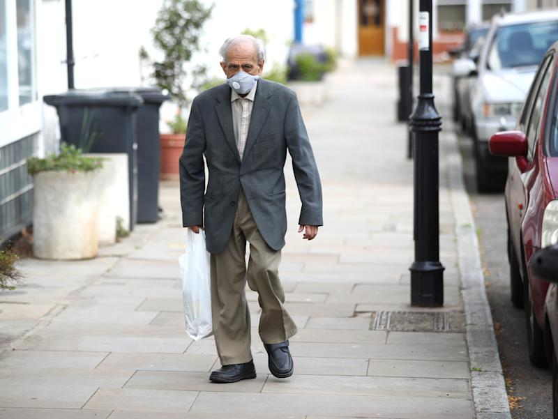 LONDON, ENGLAND - APRIL 11: An elderly man wearing a face mask walks in Islington on April 11, 2020 in London, England. The Coronavirus (COVID-19) pandemic has spread to many countries across the world, claiming over 100,000 lives and infecting over 1. 7 million people. (Photo by Julian Finney/Getty Images)