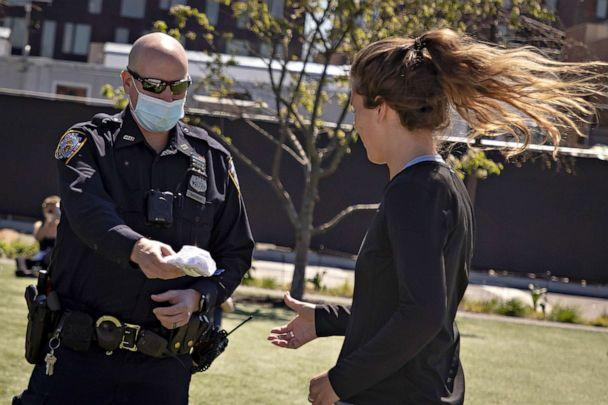 PHOTO: A police officer distributes face masks in Domino Park in the Brooklyn borough of New York City, May 2, 2020. (Gary He/EPA via Shutterstock)