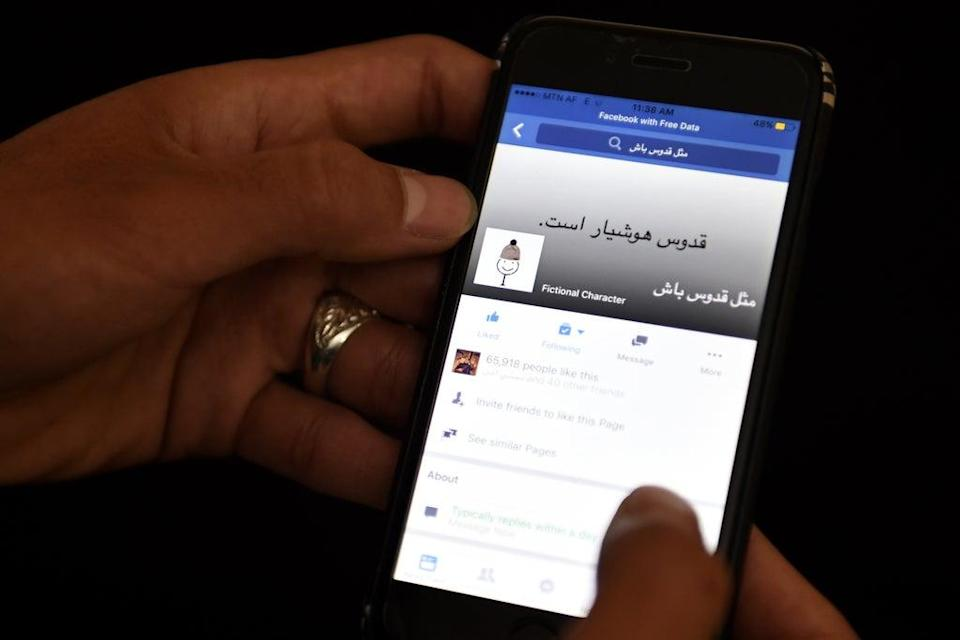 An Afghan university student looks at a meme on a Facebook account in Kabul on January 30 2016 (AFP via Getty Images)