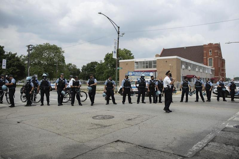 Police officers form a human barricade during an anti-police brutality protest, on 15 August in the Bronzeville neighborhood of Chicago.