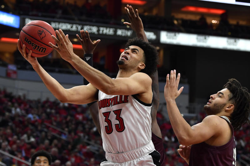 Louisville forward Jordan Nwora (33) drives in for a layup between the defensive pressure of Eastern Kentucky forward Michael Moreno (24), right, and forward Tre King (2), rear, during the second half of an NCAA college basketball game in Louisville, Ky., Saturday, Dec. 14, 2019. Louisville won 99-67. (AP Photo/Timothy D. Easley)