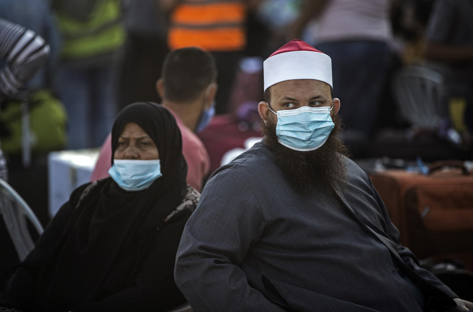 Palestinians wearing face masks sit next to their luggage, as they wait to cross to the Rafah crossing border with Egypt, southern Gaza Strip, Sunday, Sept. 27, 2020. (AP Photo/Khalil Hamra)