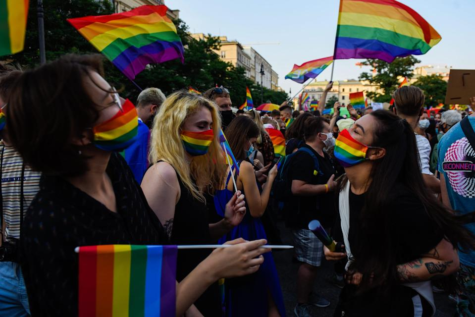 People wear protective face masks with rainbow colors and dance during the 2020 Equality March on Aug. 29, 2020, in Krakow, Poland. Growing hostility toward the LGBTQ community in Poland drew a wave of protests.