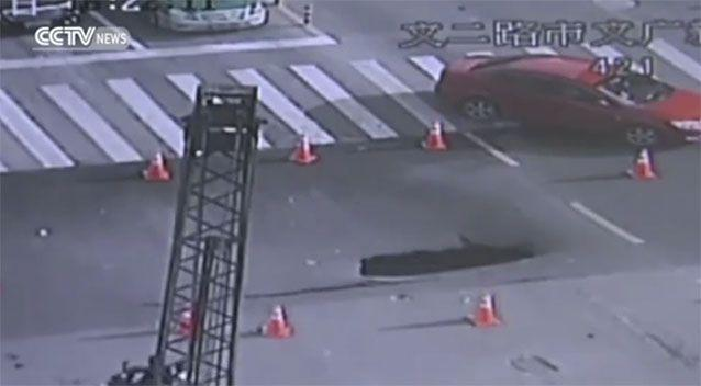 Other police arrived to section off the crack, but the sinkhole opened soon after. Source: CCTV