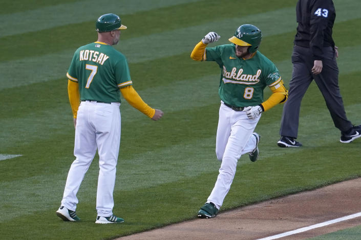 Oakland Athletics' Jed Lowrie (8) is congratulated by third base coach Mark Kotsay (7) after hitting a home run against the Kansas City Royals during the fourth inning of a baseball game in Oakland, Calif., Thursday, June 10, 2021. (AP Photo/Jeff Chiu)