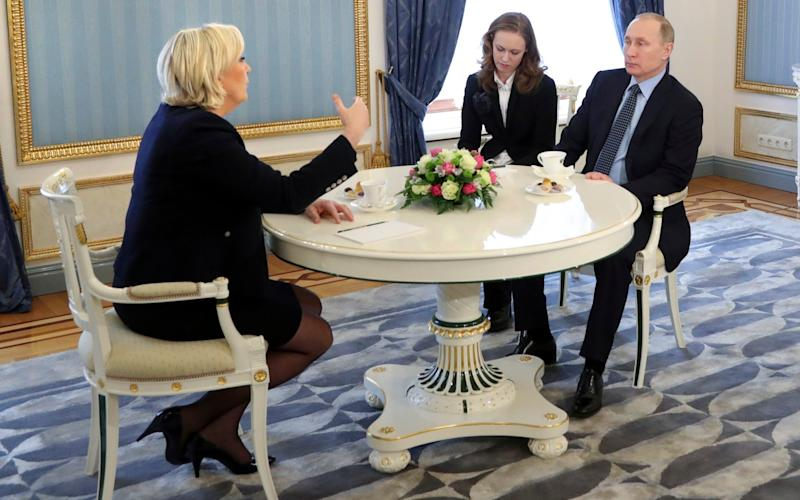 French far-right presidential candidate Marine Le Pen, left, gestures while speaking to Russian President Vladimir Putin, right, during their meeting in the Kremlin in Moscow - Credit: POOL SPUTNIK KREMLIN