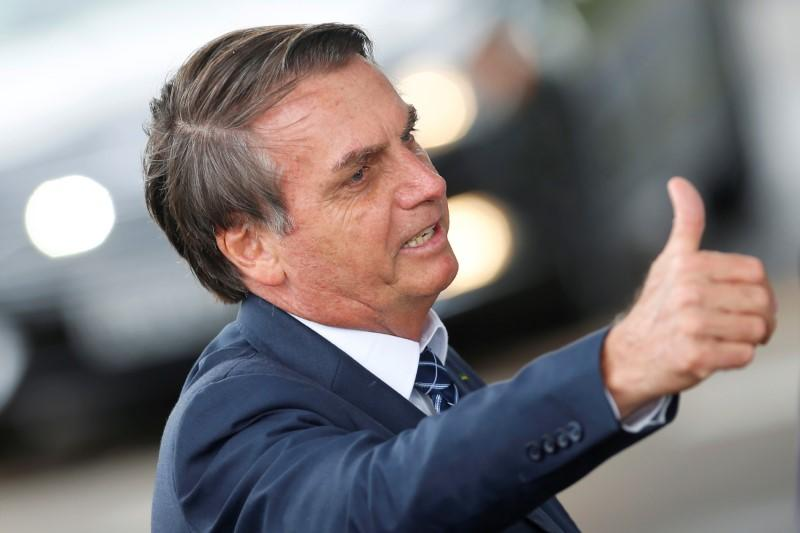 Brazil's President Jair Bolsonaro gestures as he leaves the Alvorada Palace in Brasilia