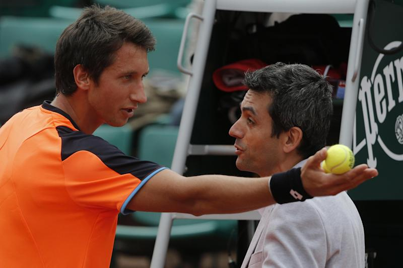 Ukraine's Sergiy Stakhovsky, left, argues the decision of the umpire to call the ball in, in his first round match against Richard Gasquet of France at the French Open tennis tournament, in Roland Garros stadium in Paris, Monday, May 27, 2013. Stakhovsky later took a picture with his smart phone of the mark of the ball on the clay court. (AP Photo/Michel Spingler)