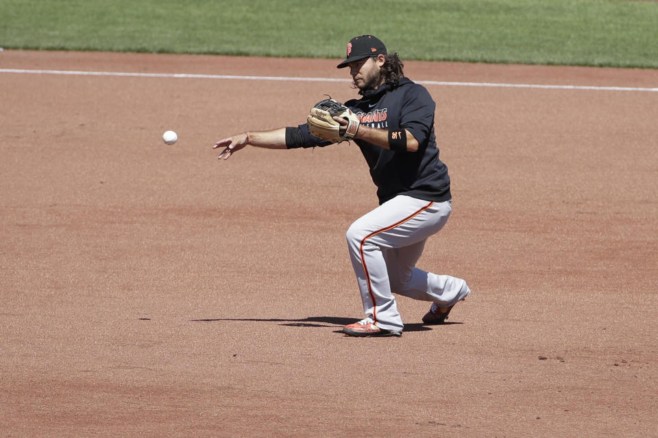 San Francisco Giants shortstop Brandon Crawford throws a ball during a baseball practice in San Francisco, Sunday, July 5, 2020. (AP Photo/Jeff Chiu)