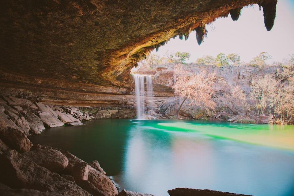 """<p>Just a short drive away from Austin, Texas, you'll find the magical (and historic) <a href=""""https://parks.traviscountytx.gov/find-a-park/hamilton-pool"""" rel=""""nofollow noopener"""" target=""""_blank"""" data-ylk=""""slk:Hamilton Pool Preserve"""" class=""""link rapid-noclick-resp"""">Hamilton Pool Preserve</a>. Hamilton Creek spills out over a limestone overhang to create a 50-foot waterfall and underlying pool, which is a popular swimming spot. It's so popular, in fact, that Travis County Parks has started taking <a href=""""https://parks.traviscountytx.gov/reservations/hamilton-pool"""" rel=""""nofollow noopener"""" target=""""_blank"""" data-ylk=""""slk:visitor reservations"""" class=""""link rapid-noclick-resp"""">visitor reservations</a> for it. </p>"""