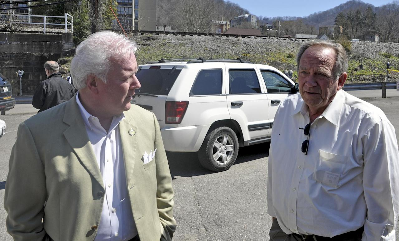 Mingo County Commissioners John Mark Hubbard and David Baisden speaks to a journalist as law enforcement officers and emergency service personnel converge on the scene of the shooting in downtown Williamson, W.Va., Wednesday, April 3, 2013, where Sheriff Eugene Crum was shot and killed at point blank range. (AP Photo/Williamson Daily News, Kyle Lovern)