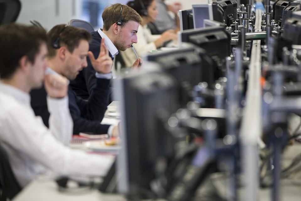 Dealers work on the IG Group trading floor in London, Britain June 30, 2015. Euro zone stocks and low-rated bonds recovered the worst of their losses on Tuesday but remained on edge as Greece looked set to default on a debt repayment to the IMF and plunge deeper into financial crisis. REUTERS/Neil Hall