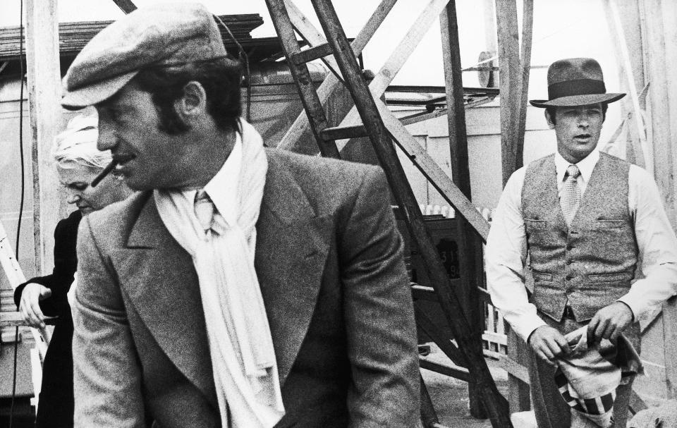 """FILE - In this 1969 file photo, French actors Jean-Paul Belmondo. left, and Alain Delon are seen during the shooting of a Jacques Deray film, """"Borsalino"""" in Marseille, France. French New Wave actor Jean-Paul Belmondo has died, according to his lawyer's office on Monday Sept. 6, 2021. (AP Photo/File)"""