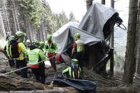 Rescuers search for evidence in the wreckage of a cable car after it collapsed near the summit of the Stresa-Mottarone line in the Piedmont region, northern Italy, Wednesday, May 26, 2021. Police have made three arrests in the cable car disaster that killed 14 people after an investigation showed a clamp, placed on the brake as a patchwork repair effort, prevented the brake from engaging after the lead cable snapped. (AP Photo/Luca Bruno)