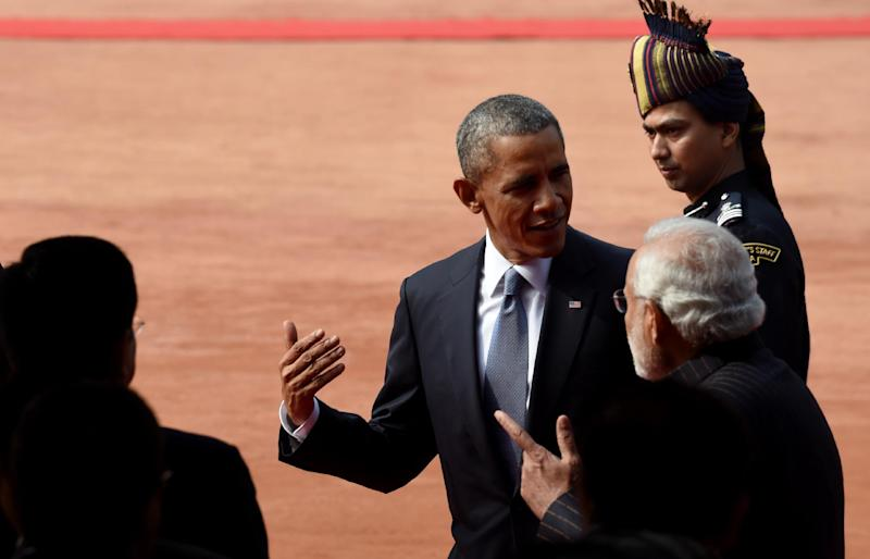 US President Barack Obama (C) speaks to Indian Prime Minister Narendra Modi as they walk through the Presidential Palace in New Delhi on January 25, 2015