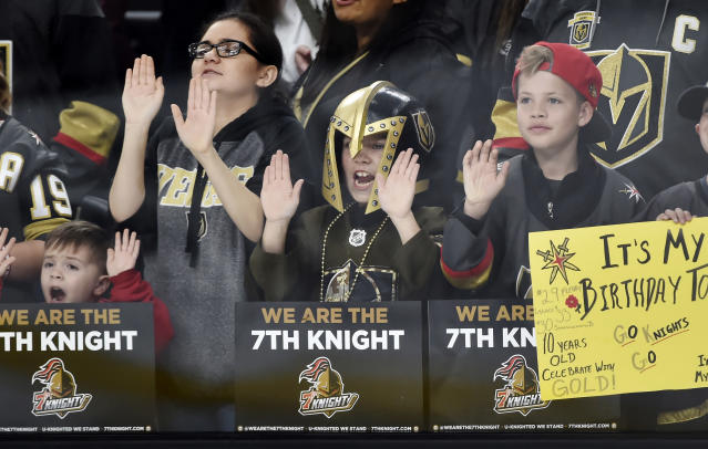 FILE - In this Feb. 13, 2018, file photo, young Vegas Golden Knights fans cheers before the start an NHL hockey game between the Vegas Golden Knights and the Chicago Blackhawks in Las Vegas. The love affair between a city and its new team wasn't totally unexpected. Las Vegas was, after all, a town starved for major league sports. (AP Photo/David Becker, File)