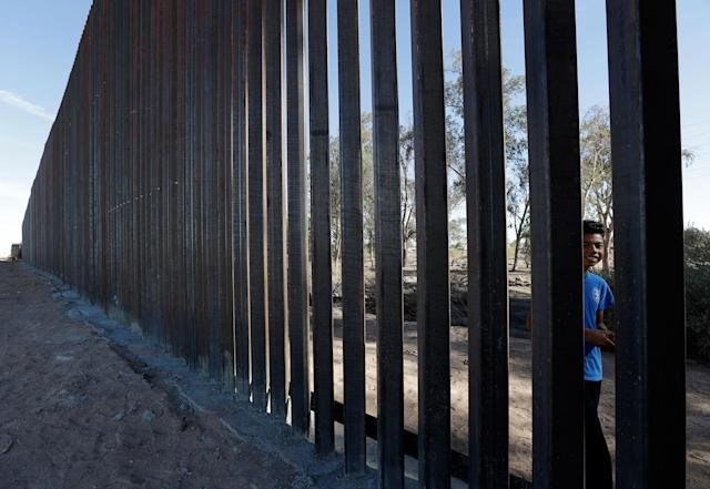 <p>A boy looks through the first section of a newly-constructed structure along the border separating Mexicali, Mexico, right, and Calexico, Calif., March 5, 2018. (Photo: Gregory Bull/AP) </p>