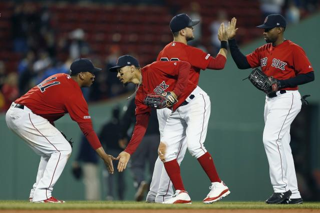 Boston Red Sox's Rafael Devers, Mookie Betts, Michael Chavis and Jackie Bradley Jr., from left, celebrate after the Red Sox defeated the Seattle Mariners 14-1 in a baseball game in Boston, Friday, May 10, 2019. (AP Photo/Michael Dwyer)