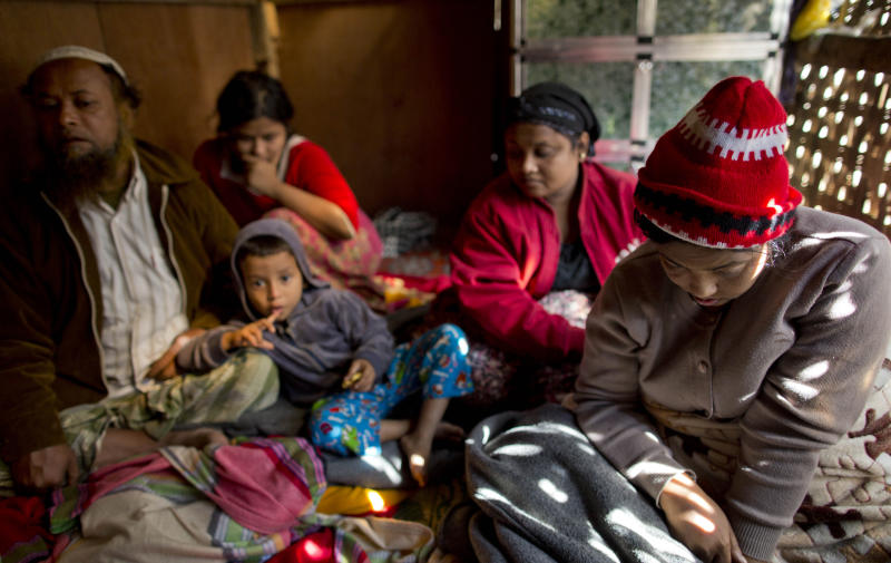 In this Jan. 17, 2014 photo, ailing Noor Jahan, right, sits with her husband Mohamad Frukan, left, and children while she suffers in pain in their living room at The' Chaung village in north of Sittwe, Rakhine state, Myanmar. As part of one of the community's richest families, Jahan, who later died, should have been in a hospital getting tests and medicine for her failing liver and kidneys, but it wasn't available to her. She was an ethnic Rohingya from Myanmar's northwestern state of Rakhine, forced to live segregated behind security checkpoints in a dirt-floor bamboo hut about a quarter mile from the sea. (AP Photo/Gemunu Amarasinghe)