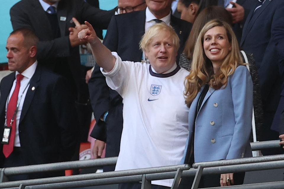 UK Prime Minister Boris Johnson and his spouse Carrie (R), are pictured ahead of the UEFA EURO 2020 semi-final football match between England and Denmark at Wembley Stadium in London on July 7, 2021. (Photo by CARL RECINE / POOL / AFP) (Photo by CARL RECINE/POOL/AFP via Getty Images)