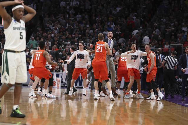 Michigan State guard Cassius Winston (5) walks off the court as Syracuse celebrates a 55-53 win in a second-round game in the NCAA men's college basketball tournament Sunday, March 18, 2018, in Detroit. (AP Photo/Carlos Osorio)