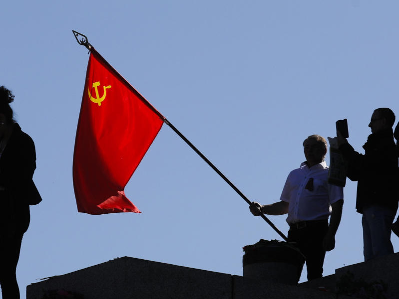 FILE - In this file photo dated Saturday, May 9, 2020, a man holds a Soviet flag during a ceremony at the Soviet War memorial to mark the 75th anniversary of Victory Day at the district Treptow in Berlin, Germany. An influential committee of British lawmakers plans to publish its findings Tuesday July 21, 2020, reporting on Russian interference in British politics, amid criticism the government delayed its release for more than six months to shield Prime Minister Boris Johnson and his Conservative Party from embarrassment. (AP Photo/Markus Schreiber, FILE)