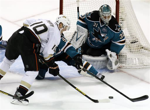 Anaheim Ducks' Corey Perry (10) shoots as San Jose Sharks' Jason Demurs (5), center, and goalie Antti Niemi defend during the second period of an NHL hockey game, Wednesday, March 27, 2013 in San Jose, Calif. (AP Photo/George Nikitin)