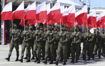 Polish soldiers hold national flags as Poland marks the centennial of the Battle of Warsaw, a Polish military victory in 2020 that stopped the Russian Bolshevik march toward the west, in Warsaw, Poland, Saturday Aug. 15, 2020. U.S. Secretary of State Mike Pompeo attended as he wrapped up a visit to central Europe. (AP Photo/Czarek Sokolowski)