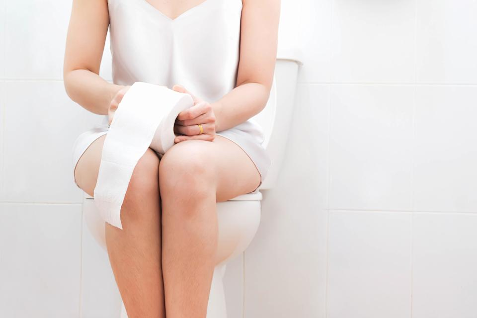 Women wearing white sleepwear, Sitting on the toilet Hand holding the tissue, health care concept