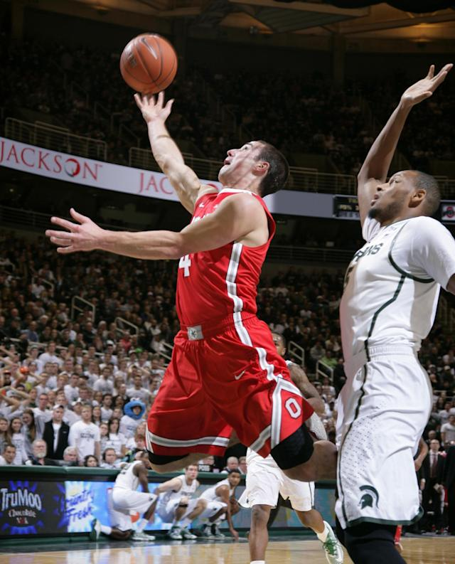 Ohio State's Aaron Craft, left, puts up a layup against Michigan State's Adreian Payne during the first half of an NCAA college basketball game, Tuesday, Jan. 7, 2014, in East Lansing, Mich. (AP Photo/Al Goldis)