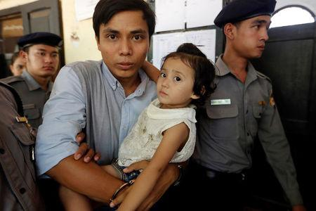 Detained Reuters journalist Kyaw Soe Oo, handcuffed, carries his daughter Moe Thin Wai Zin while arriving at a court hearing in Yangon, Myanmar May 16, 2018. REUTERS/Ann Wang