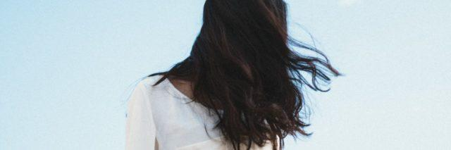 photo of woman with dark hair stood against blue sky with face hidden by her hair
