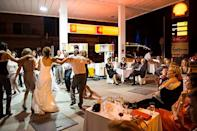 "<div class=""caption-credit""> Photo by: Nick Hannes</div><div class=""caption-title"">5. At a Gas Station</div>Photographer Nick Hannes stumbled upon an unusual sight while visiting Greece - <a href=""http://www.bridalguide.com/blogs/bridal-buzz/craziest-weddings-2012"" rel=""nofollow noopener"" target=""_blank"" data-ylk=""slk:a wedding at a gas station"" class=""link rapid-noclick-resp""><b>a wedding at a gas station</b></a> . To cut costs, Anna and Christos Karalis held their reception at the station owned by the groom, where they danced the night away with their friends and family. A family member told Hannes, ""This is how we respond to the crisis ... A Greek keeps on laughing and celebrating, even when his money is being taken away."""