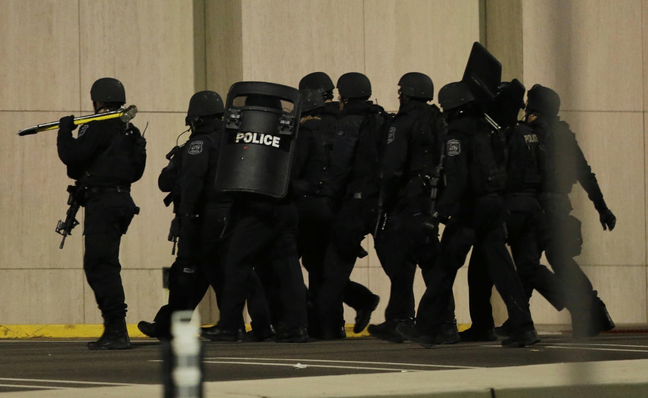 Officials wearing tactical gear walk outside of Garden State Plaza Mall following reports of a shooter, Monday, Nov. 4, 2013, in Paramus, N.J. Hundreds of law enforcement officers converged on the mall Monday night after witnesses said multiple shots were fired there. (AP Photo/Julio Cortez)