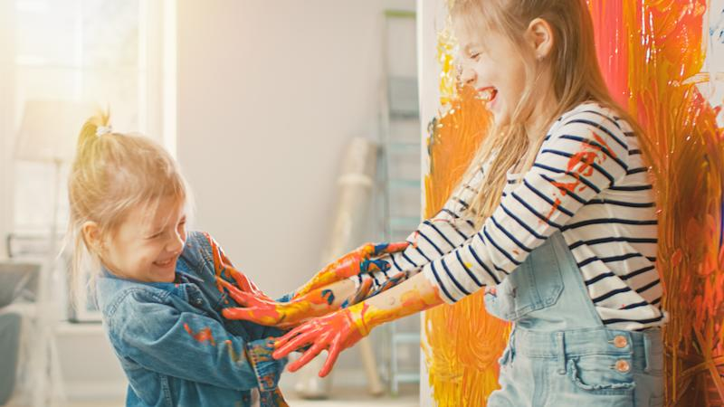 Two Fun Little Sisters Play and Fool Around with Their Hands Dipped in Colorful Paint. They are Happy and Laugh. Sisterhood Goals. Redecoration at Home.