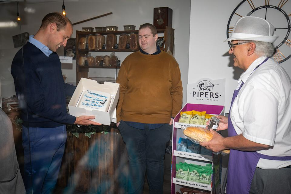 Britain's Prince William, Duke of Cambridge, is presented by shop owner Paul Brandon (R) with a birthday cake, who will be 38 on June 21, during a visit to Smiths the Bakers in the High Street in King's Lynn, eastern England on on June 19, 2020. - The Duke visited the independent business to hear about the impact of the Covid-19 pandemic. (Photo by Aaron Chown / POOL / AFP) (Photo by AARON CHOWN/POOL/AFP via Getty Images)
