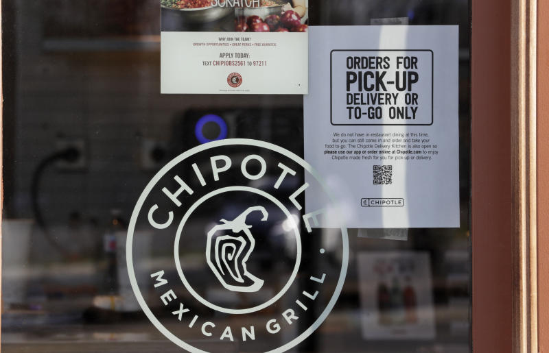 """A sign hangs in the window at Chipotle Mexican Grill, Monday, March 16, 2020, in Woodmere Village, Ohio. All bars and restaurants in Ohio will be closed until further notice, said Gov. Mike DeWine, who is taking a tough stance on trying to stem the coronavirus saying """"if we don't take these actions now, it'll be too late."""" (AP Photo/Tony Dejak)"""