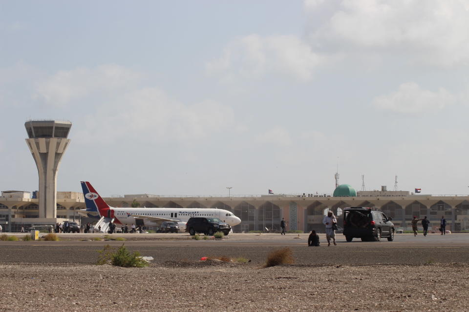 Bystanders stand near the runway of Yemen southern city of Aden's airport shortly after an explosion hit as a government plane landed, Wednesday, Dec. 30, 2020. The blast struck the airport building shortly after a Yemenia airlines plane carrying the newly formed Cabinet landed. No one on the government plane was hurt. (AP Photo/Wael Qubady)