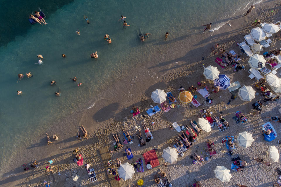 Holidaymakers enjoy the weather on a beach, in Dubrovnik, Croatia, Friday, Aug. 13, 2021. Summer tourism has exceeded even the most optimistic expectations in Croatia this year. Beaches along the country's Adriatic Sea coastline are swarming with people. Guided tours are fully booked, restaurants are packed and sailboats were chartered well in advance. (AP Photo/Darko Bandic)